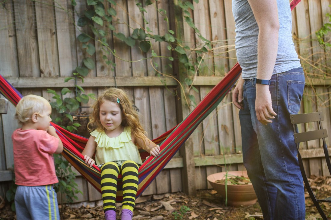 two kids and dad play with a colourful hammock