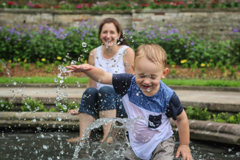 Little boy splashing in fountain by Sharon-Troy Baldwin Documentary Family Photography
