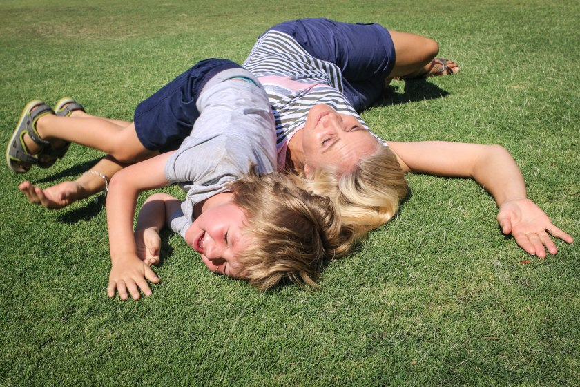 Mother and son rolling in the grass on a sunny day by Sharon Troy-Baldwin Documentary Family Photography
